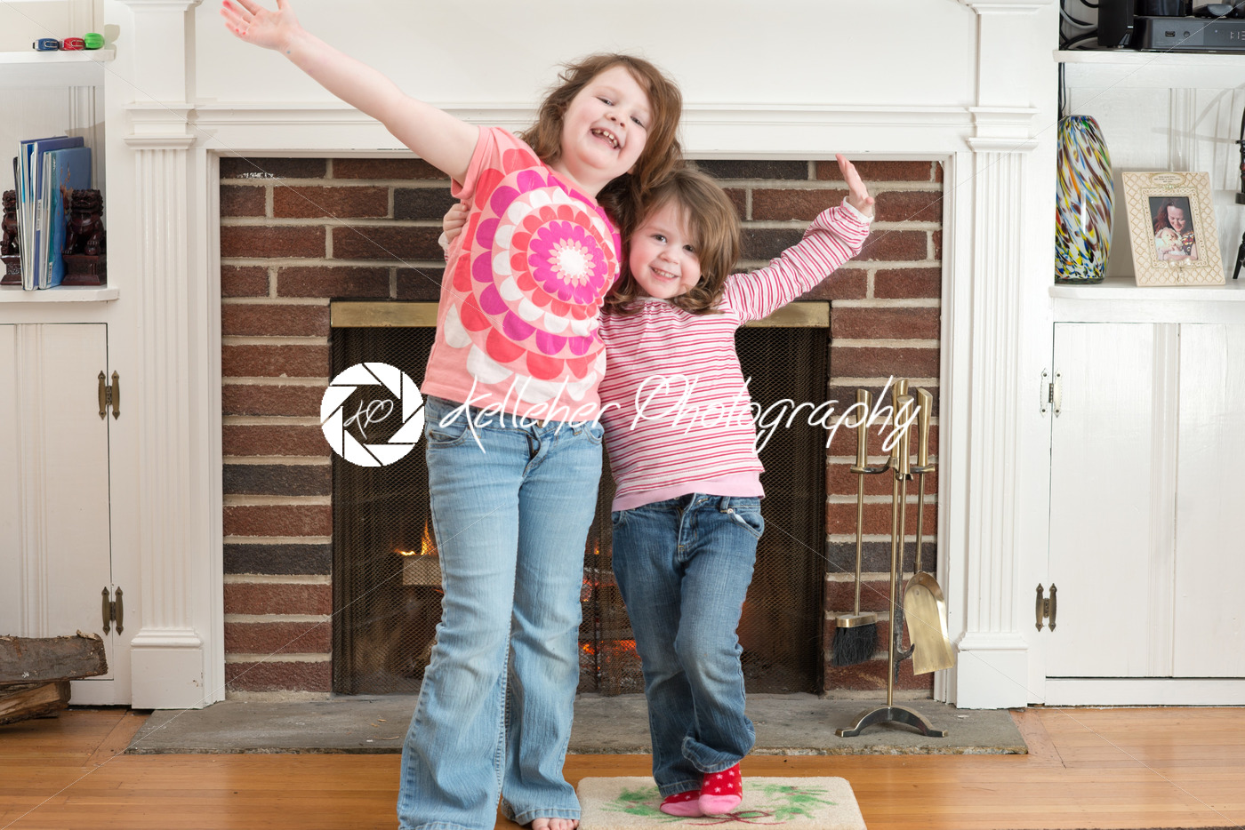 Portrait of a two young smiling sibling girls in front of a fireplace dressed for valentine's day - Kelleher Photography Store