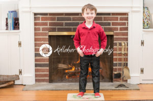 Portrait of a young smiling boy in front of a fireplace dressed for valentine's day - Kelleher Photography Store