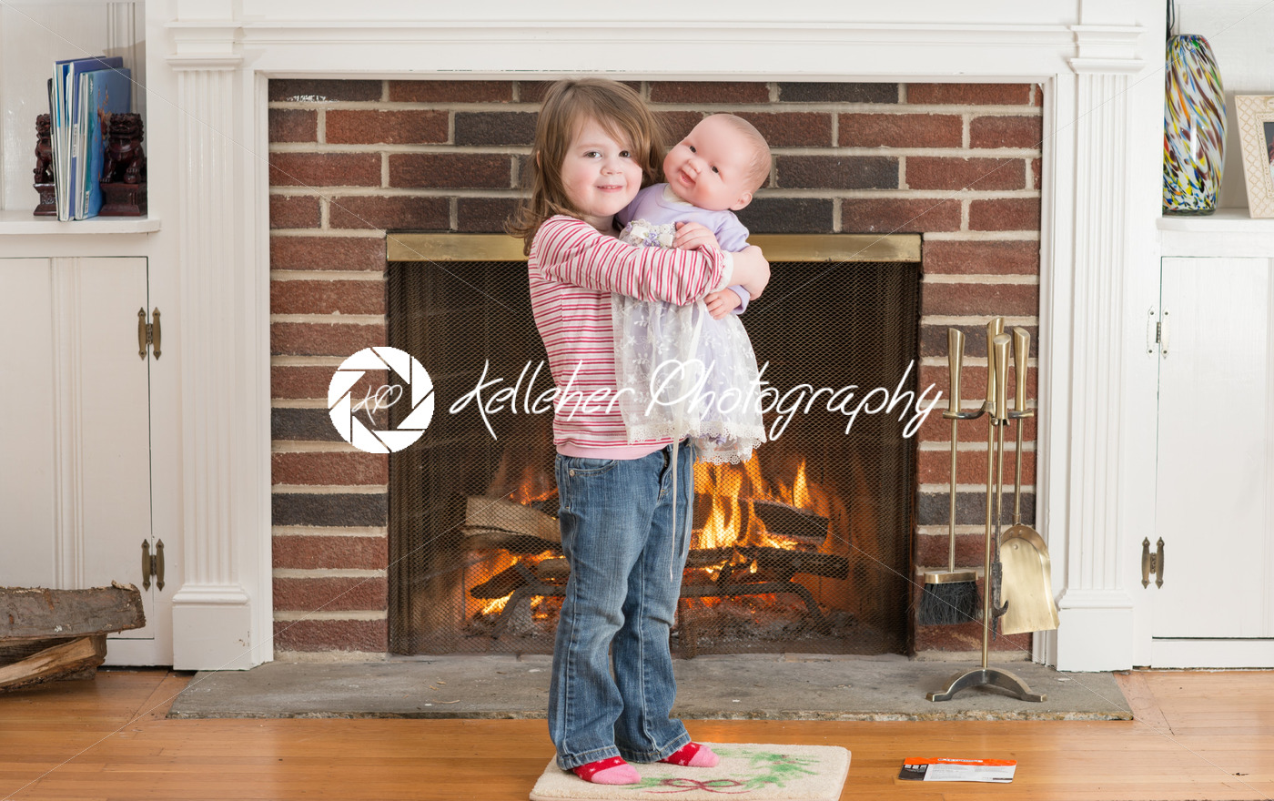 Portrait of a young smiling girl hold a baby doll in front of a fireplace dressed for valentine's day - Kelleher Photography Store