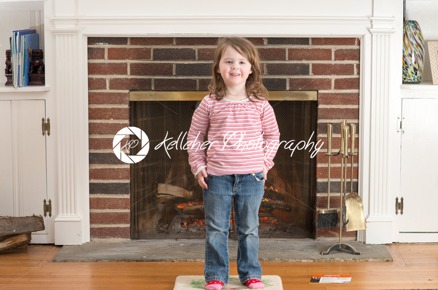 Portrait of a young smiling girl in front of a fireplace dressed for valentine's day - Kelleher Photography Store
