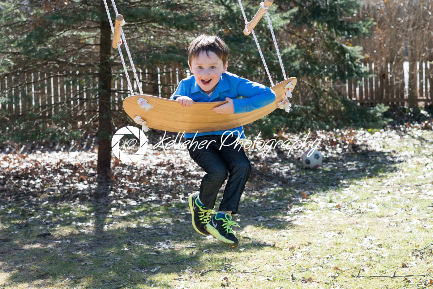 Young boy outside in backyard having fun on a swing - Kelleher Photography Store