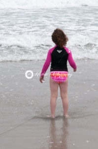Young cute little girl playing at the seaside running into the surf on a sandy beach in summer sunshine - Kelleher Photography Store