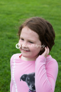 Young girl outside with hand in her hair - Kelleher Photography Store