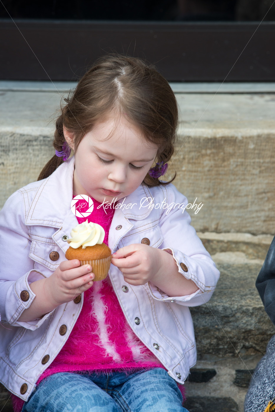Young girl sitting outside eating a cupcake - Kelleher Photography Store