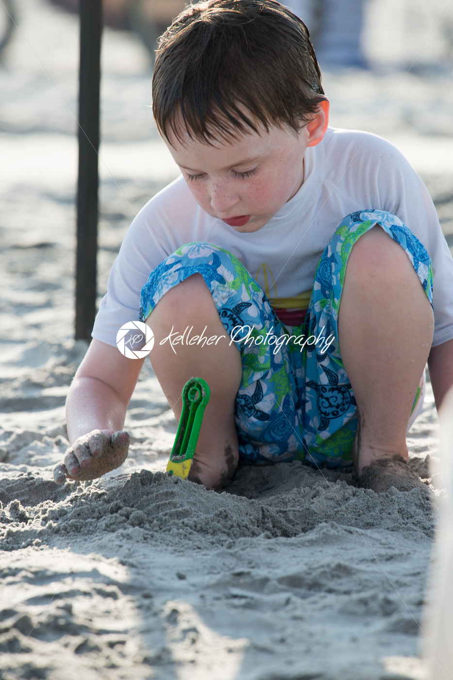 Young little boy playing with the sand and building sandcastle at the beach near the sea. - Kelleher Photography Store