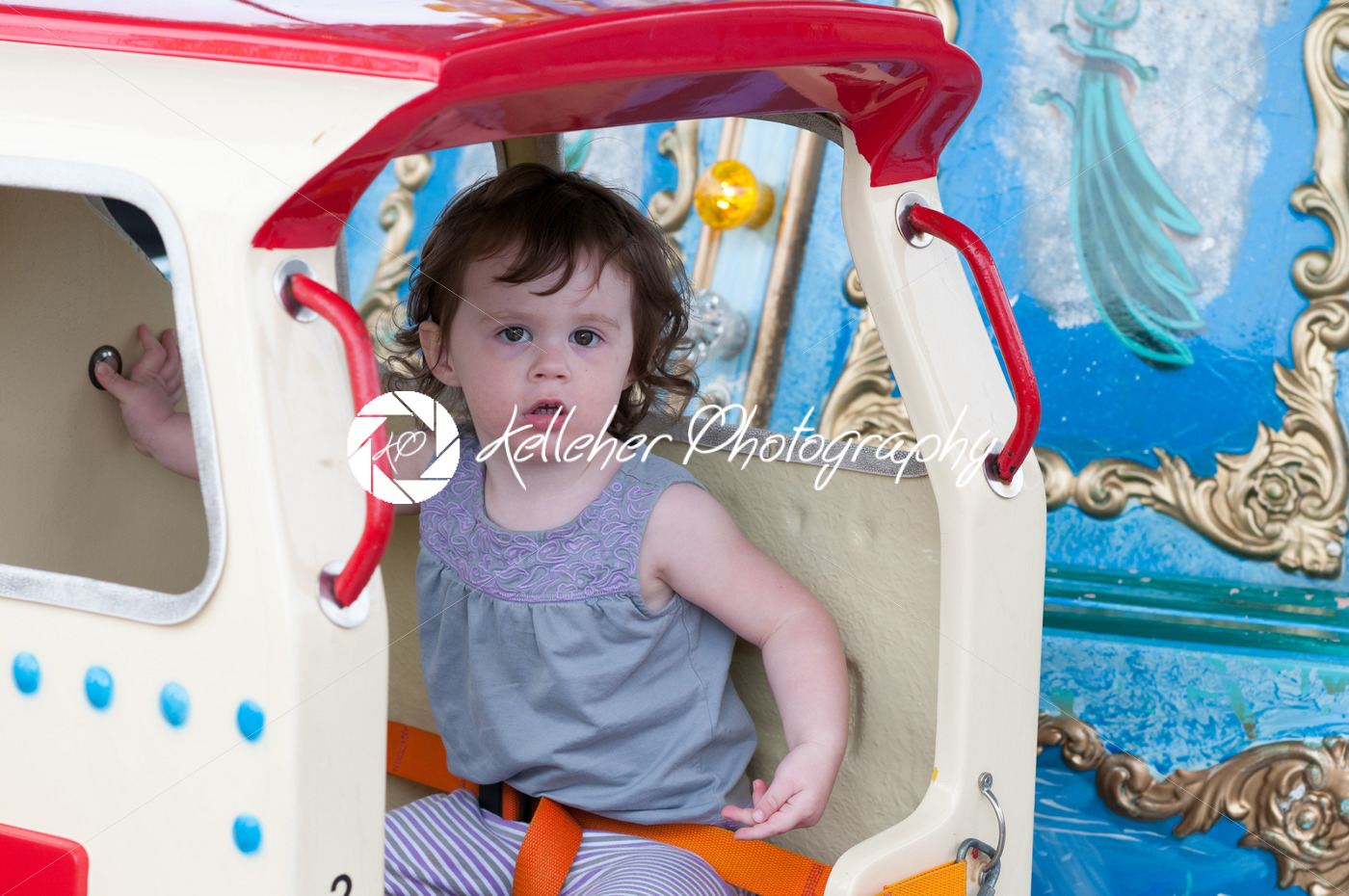 Young toddler girl having fun on boardwalk amusement ride - Kelleher Photography Store