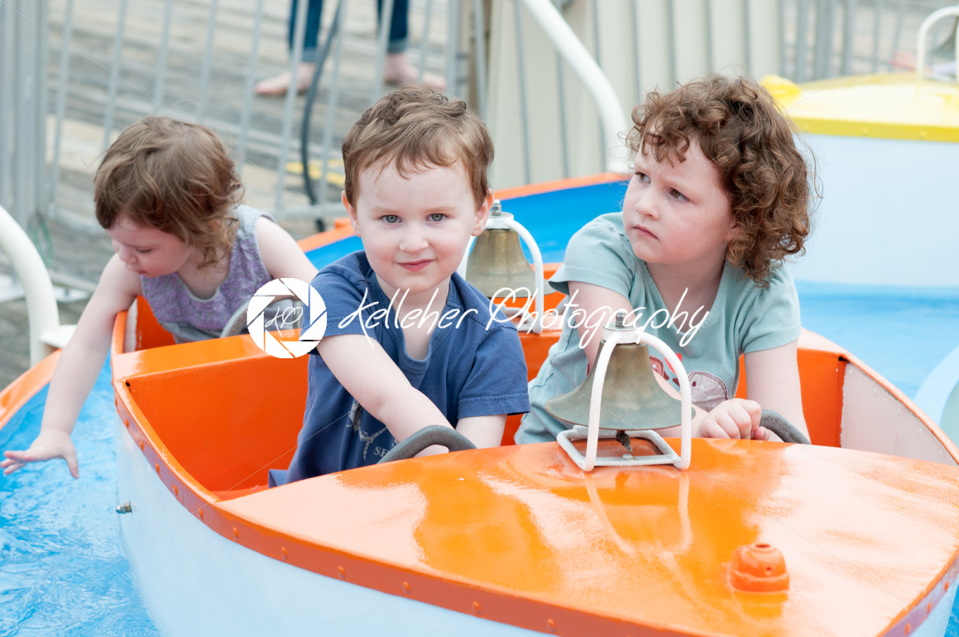 Young toddler sibblings having fun on boardwalk amusement ride - Kelleher Photography Store
