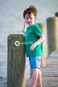 young boy standing on a wooden rustic dock holding a stick on a warm summer day. - Kelleher Photography Store