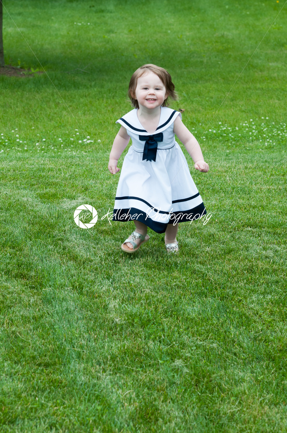 Portrait of a cute adorable little girl child in dress running on grass - Kelleher Photography Store