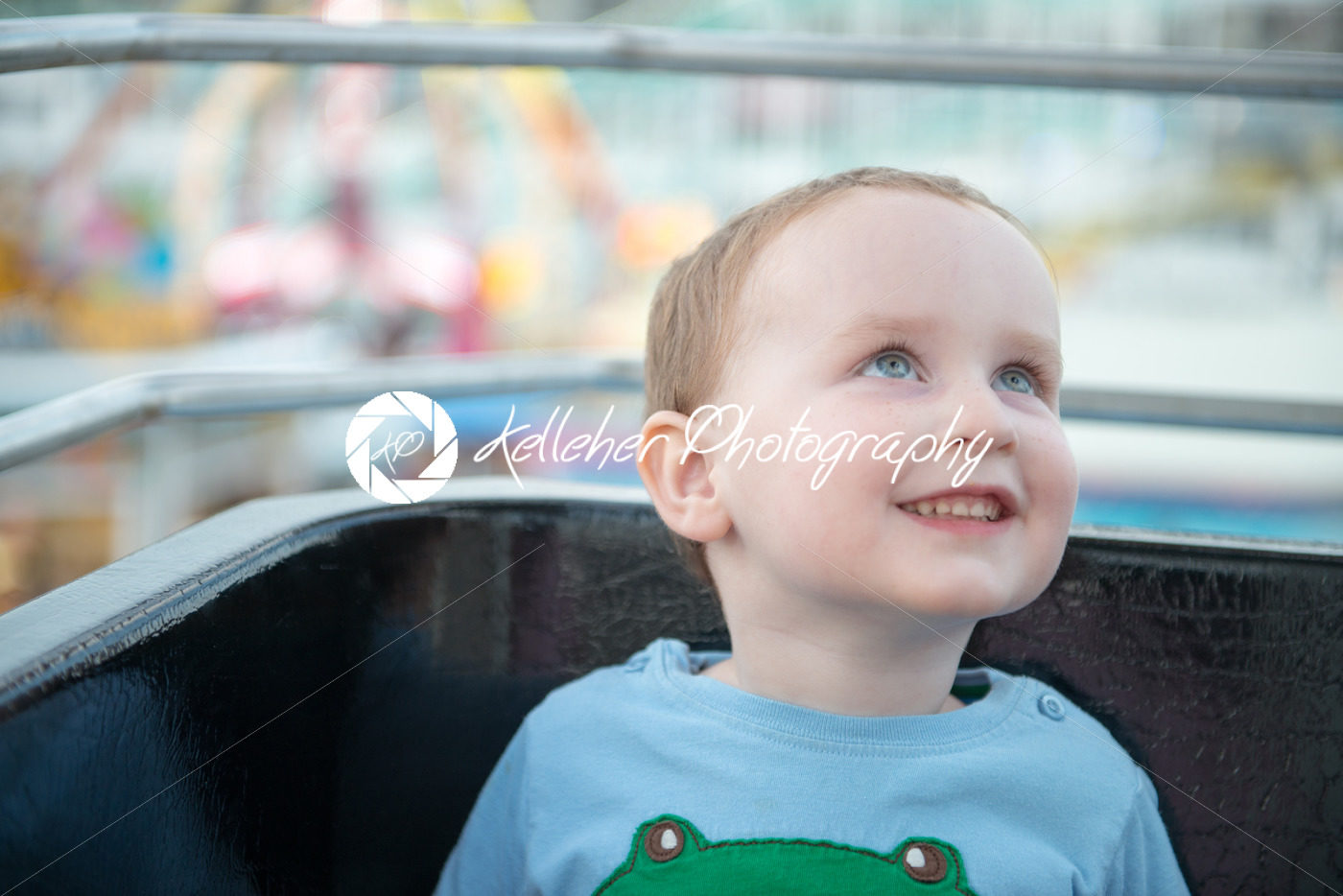 Young boy on boardwalk amusement ride ferris wheel looking up - Kelleher Photography Store