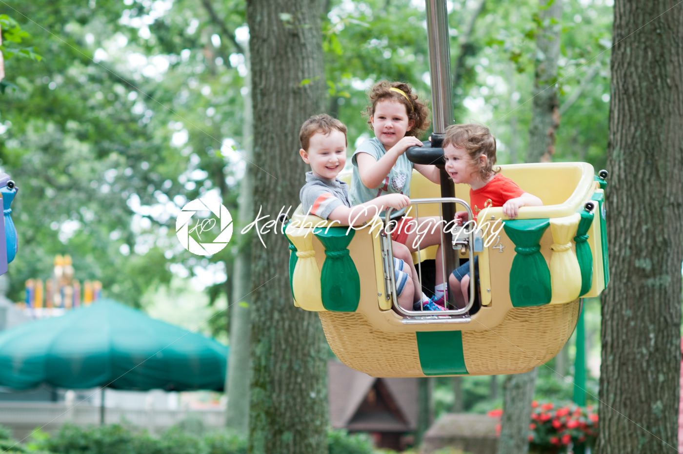 Young siblings, 1 boy and 2 girls, having fun on boardwalk amusement ride - Kelleher Photography Store