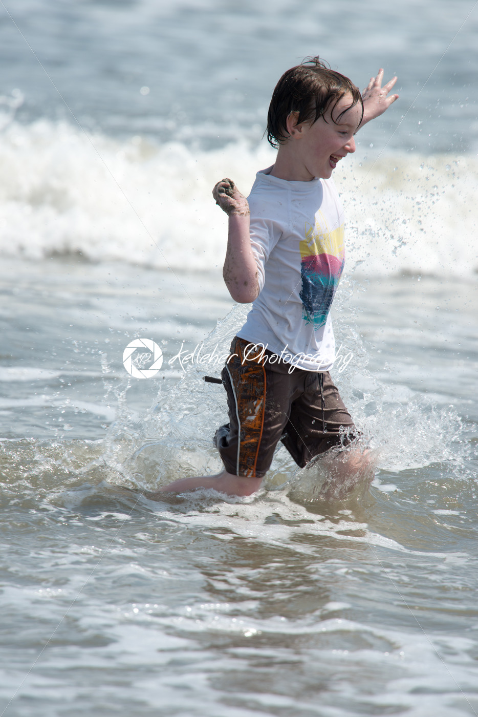 A happy young boy child running playing and having fun in the surf and waves of a sandy sunny beach - Kelleher Photography Store