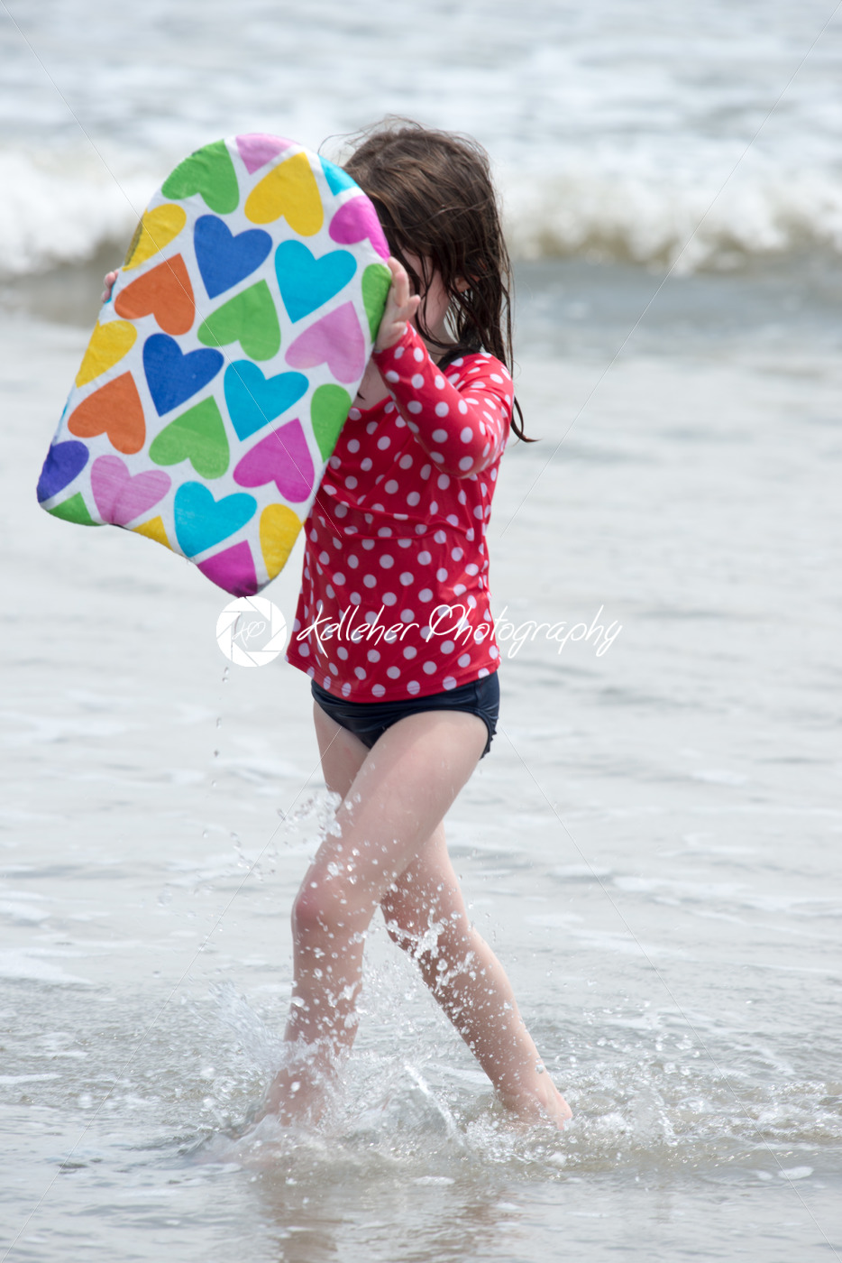 Girl coming out of the ocean waves with a boogy board - Kelleher Photography Store