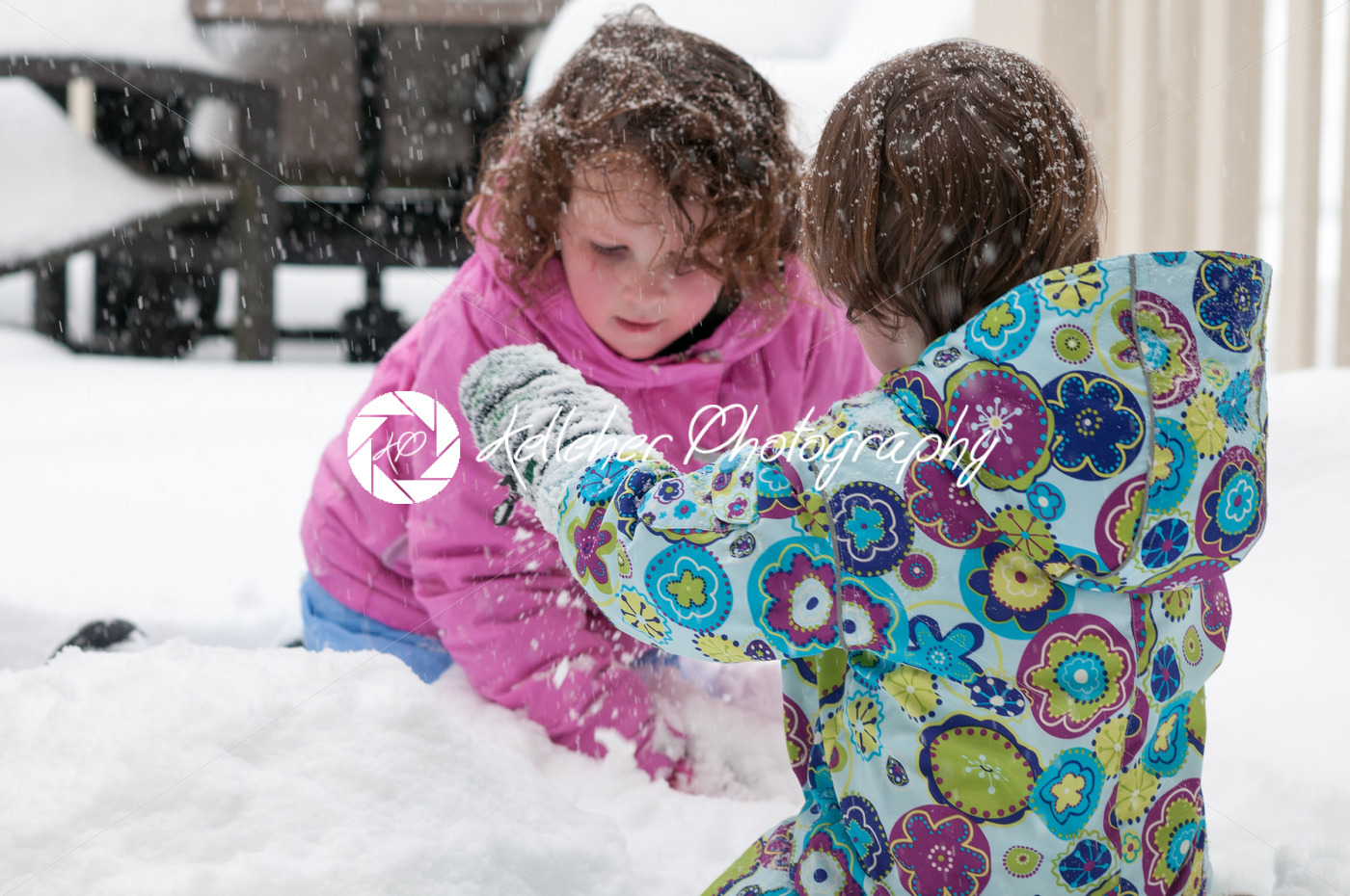 Happy toddler sibling girls in warm coat and knitted hat tossing up snow and having a fun in the winter outside, outdoor portrait - Kelleher Photography Store