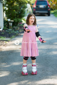 Young girl outside learning to riding on roller skates on driveway wearing protective elbow, wrist and knee pads - Kelleher Photography Store