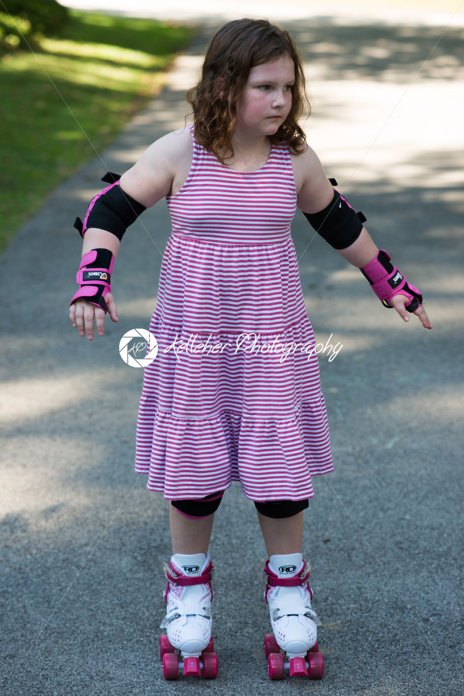 young girl outside learning to riding on roller skates on