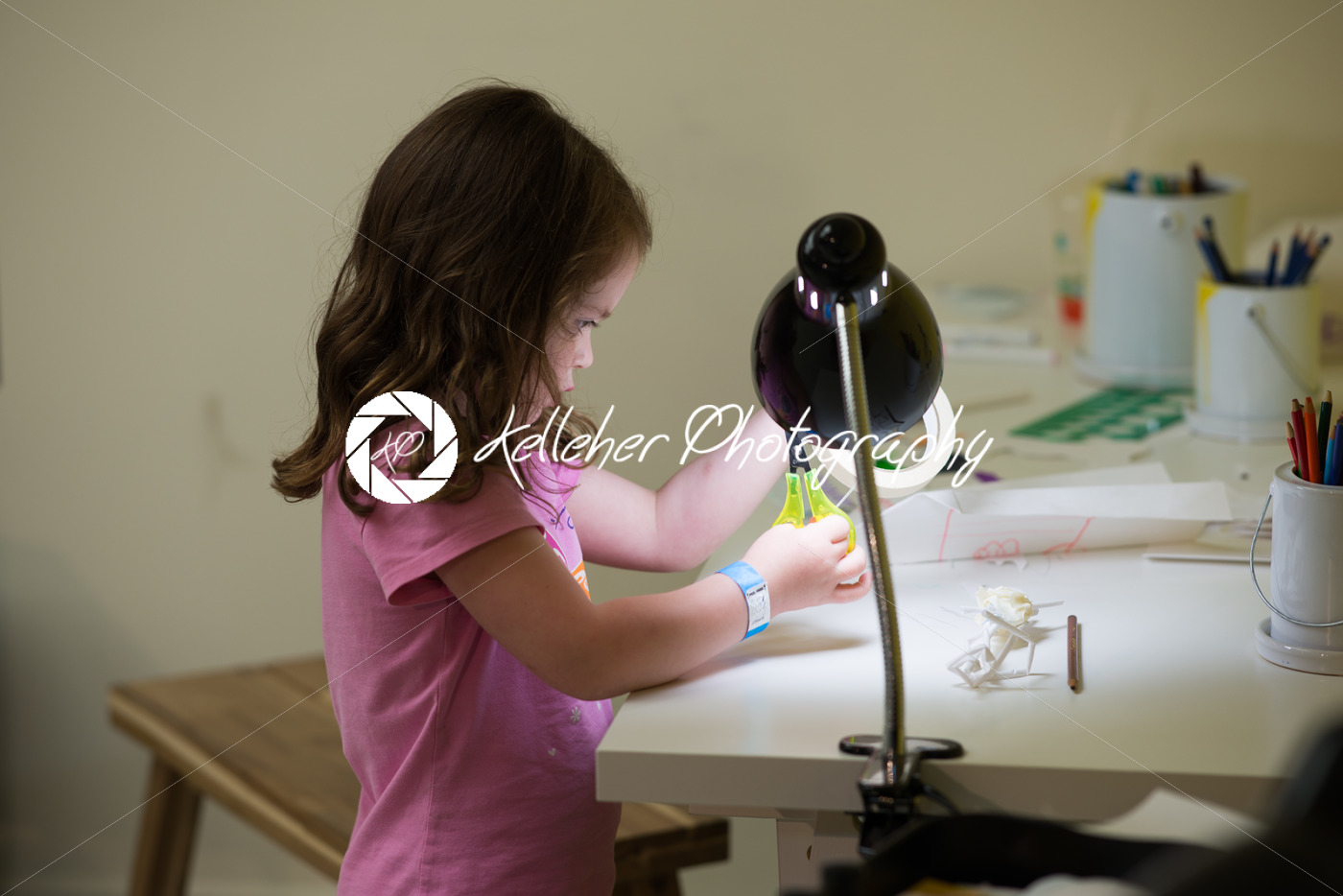 Young girl cutting tape at desk - Kelleher Photography Store