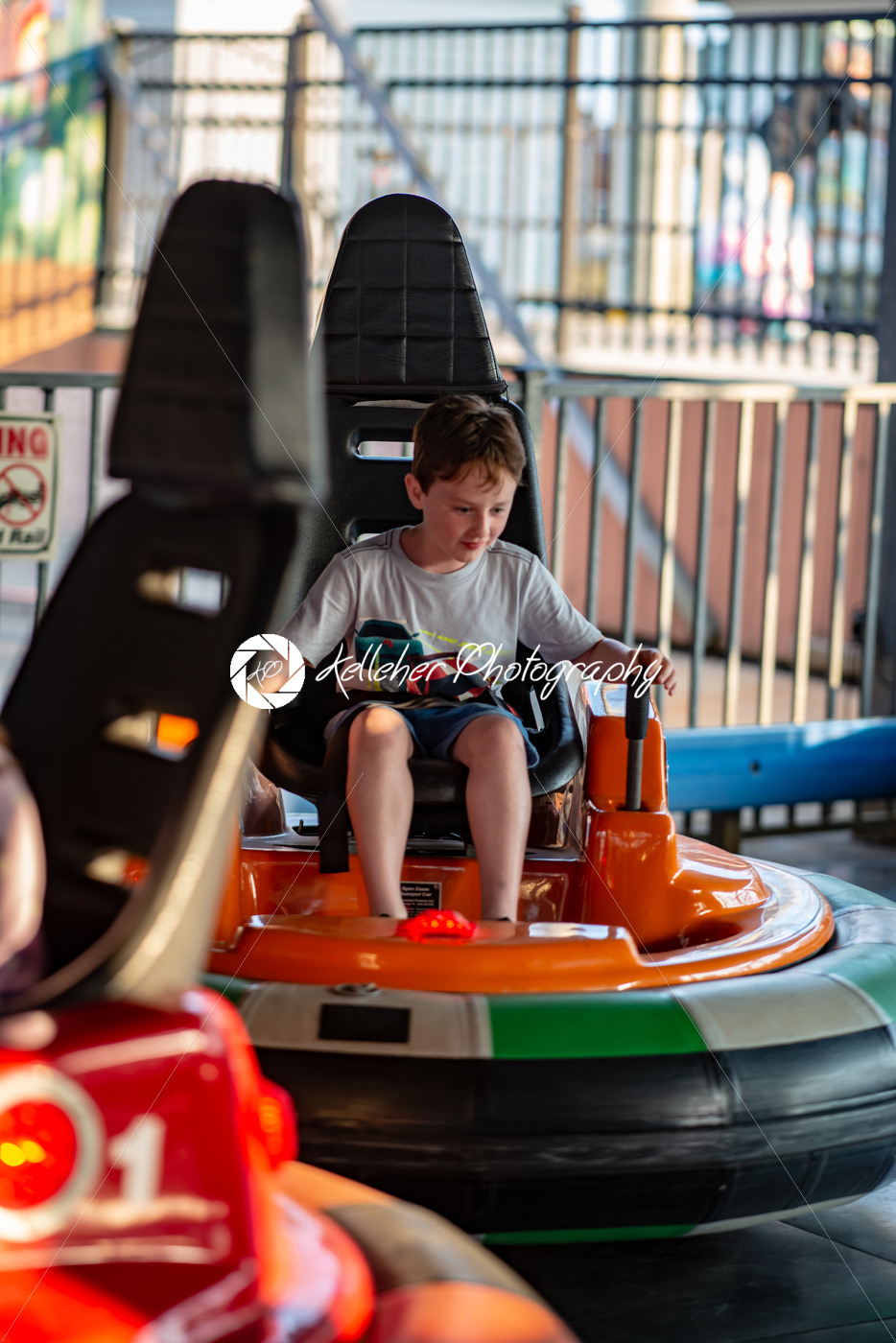Happy young boy rides electric bumper car amusement ride on shore boardwalk - Kelleher Photography Store