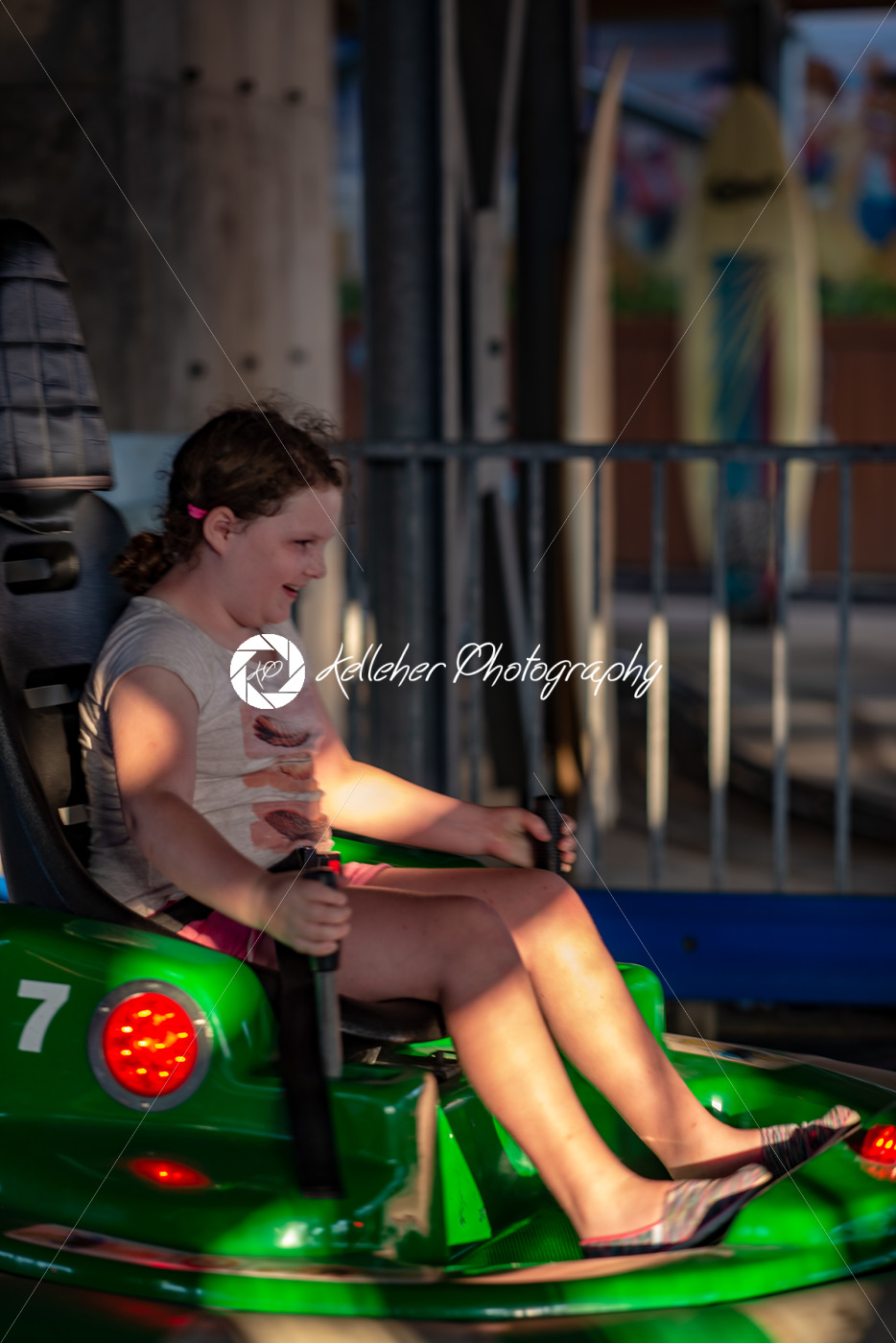 Happy young girl rides electric bumper car amusement ride on shore boardwalk - Kelleher Photography Store