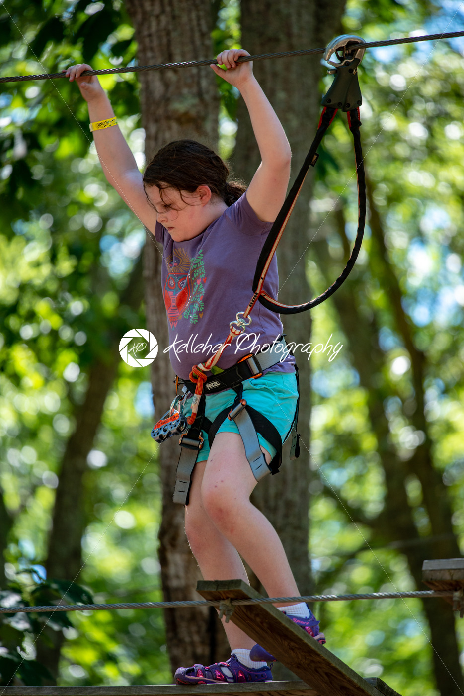 Portrait of a beautiful girl on a rope park among trees. Children summer activities. - Kelleher Photography Store