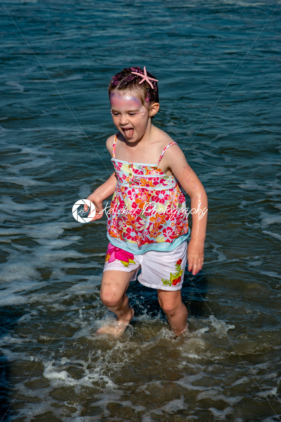 Portrait of a beautiful young mermaid girl playing in the ocean surf at the beach on a sunny day - Kelleher Photography Store
