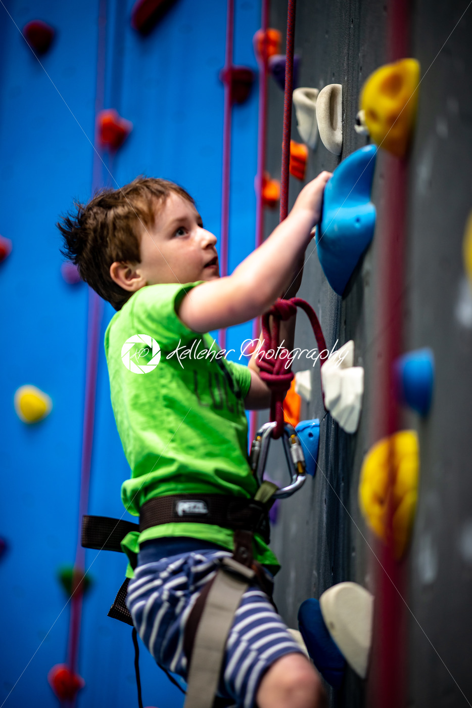 Young boy climbing up on practice wall in indoor rock gym - Kelleher Photography Store