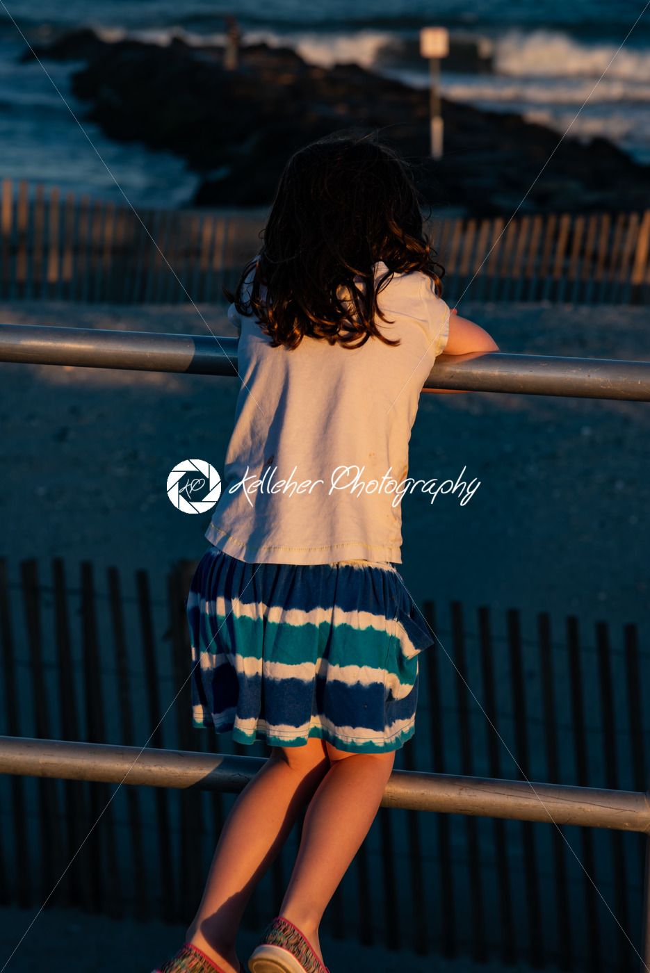 Young cute little girl on the boardwalk with back to camera looking towards the ocean surf - Kelleher Photography Store