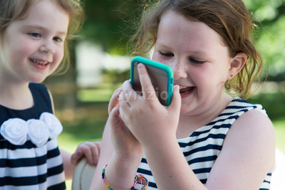 Happy Laughing Children Playing with Smartphone Outside Stock Photo