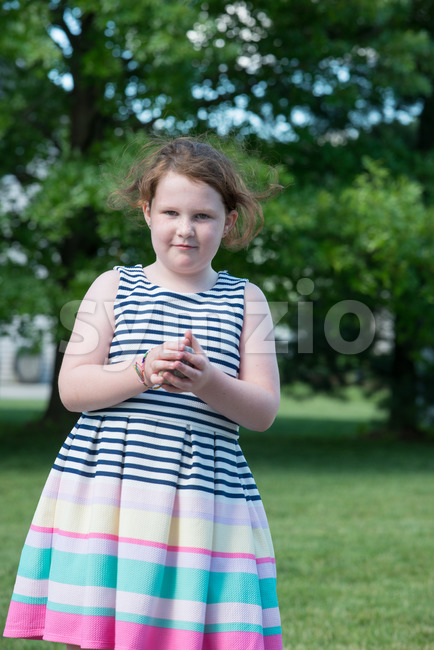 Portrait of Young Girl Standing in Backyard Stock Photo