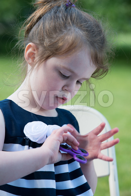 Young Girl Playing with Fidget Hand Spinner Stock Photo