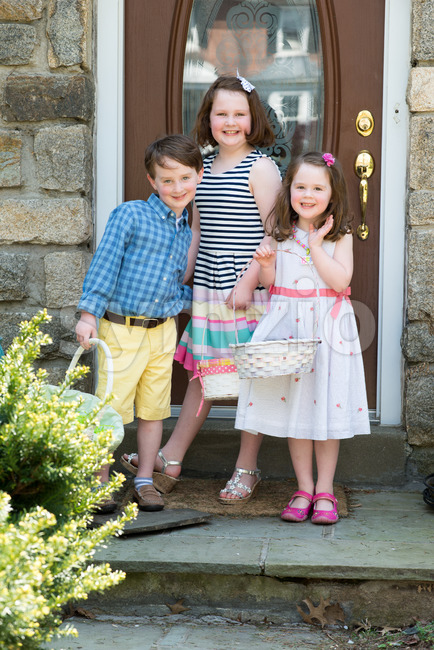 Young Siblings Outside Dressed Up for Easter holding Baskets Stock Photo