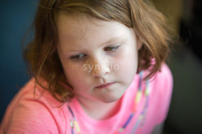 Close Portrait of Girl Thinking Sitting Down Stock Photo