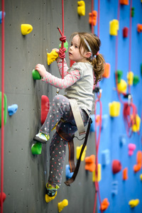 little girl climbing a rock wall indoor Stock Photo