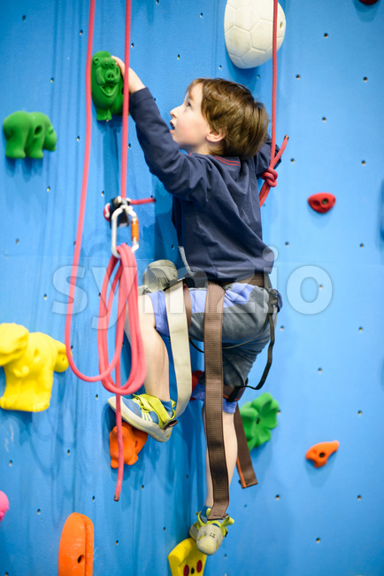 little boy climbing a rock wall indoor Stock Photo