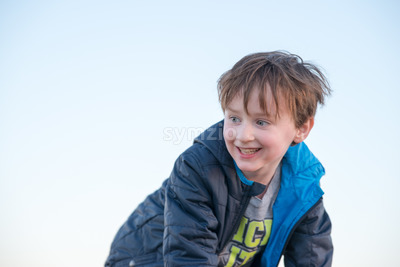 Handsome young boy outside smiling at sunset golden hour Stock Photo