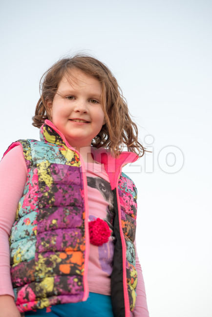 Beautiful young girl outside smiling at sunset golden hour Stock Photo