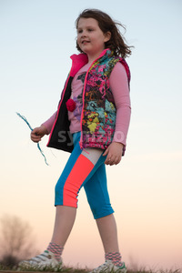 Beautiful young girl outside walking and smiling at sunset golden hour Stock Photo