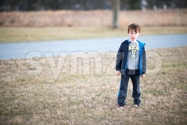 young boy outside pouting and angry at sunset golden hour Stock Photo