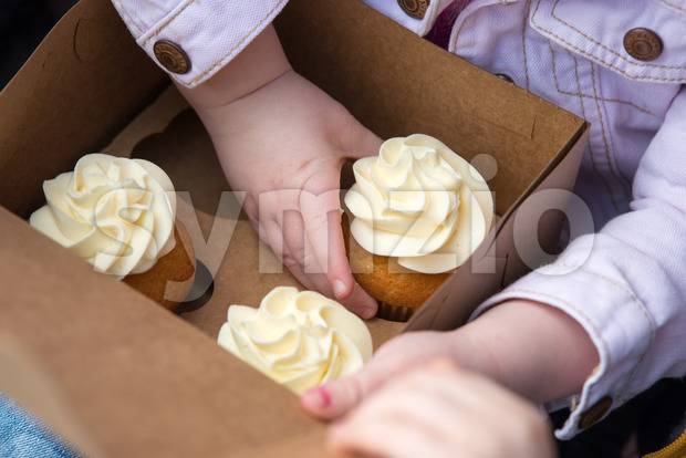 Young girl sitting outside eating a cupcake Stock Photo
