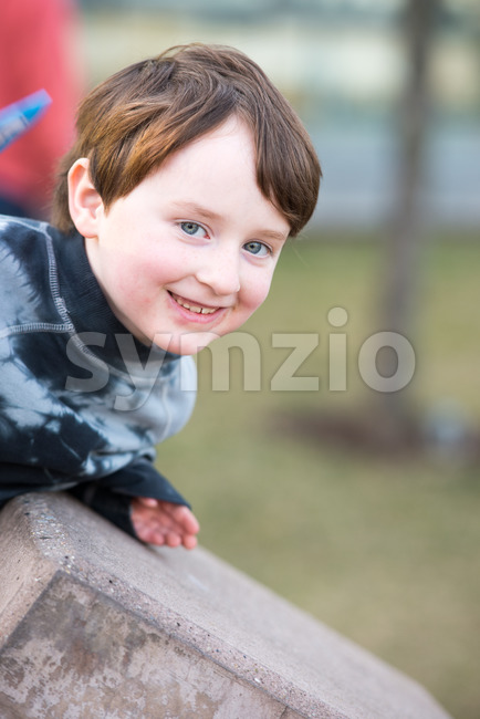 Young boy leaning over looking and smiling Stock Photo