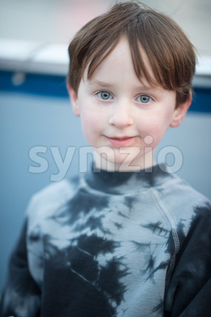 Young boy outside on boat looking happy Stock Photo