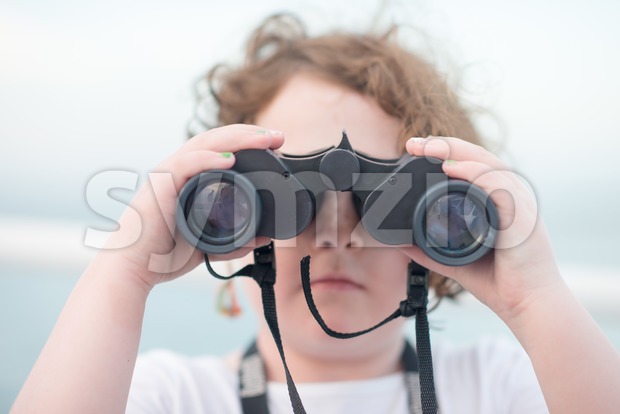 Beautiful young girl on boat looking directly at camera through binoculars Stock Photo