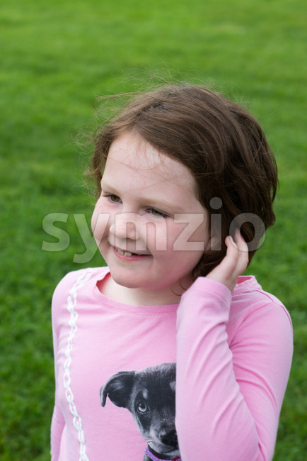 Young girl outside with hand in her hair Stock Photo