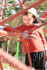 Young boy child playing at outdoor playground climbing net Stock Photo