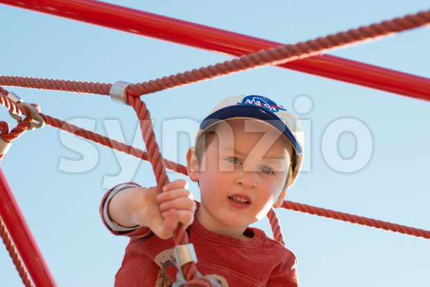 A Young boy child playing at outdoor playground climbing net