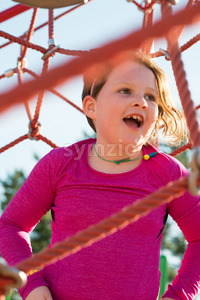Young girl child playing at outdoor playground climbing net Stock Photo