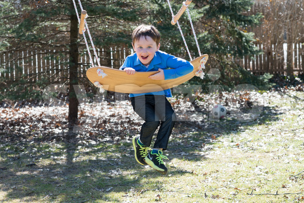Young boy outside in backyard having fun on a swing Stock Photo