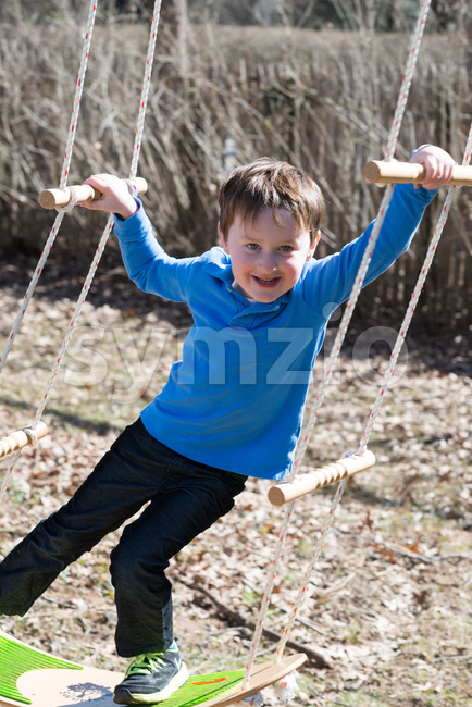 A Young boy outside in backyard having fun on a swing