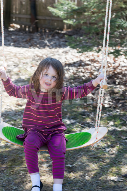 Young girl outside in backyard having fun on a swing Stock Photo