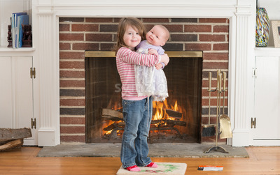 Portrait of a young smiling girl hold a baby doll in front of a fireplace dressed for valentine's day Stock Photo